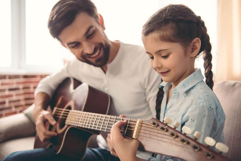 Vater unterrichtet Tochter beim Gitarrespielen