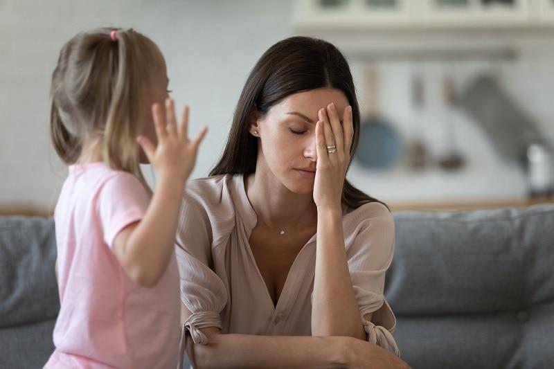 depressive Mutter reibt sich das Gesicht, als ihre Tochter versucht, mit ihr zu sprechen