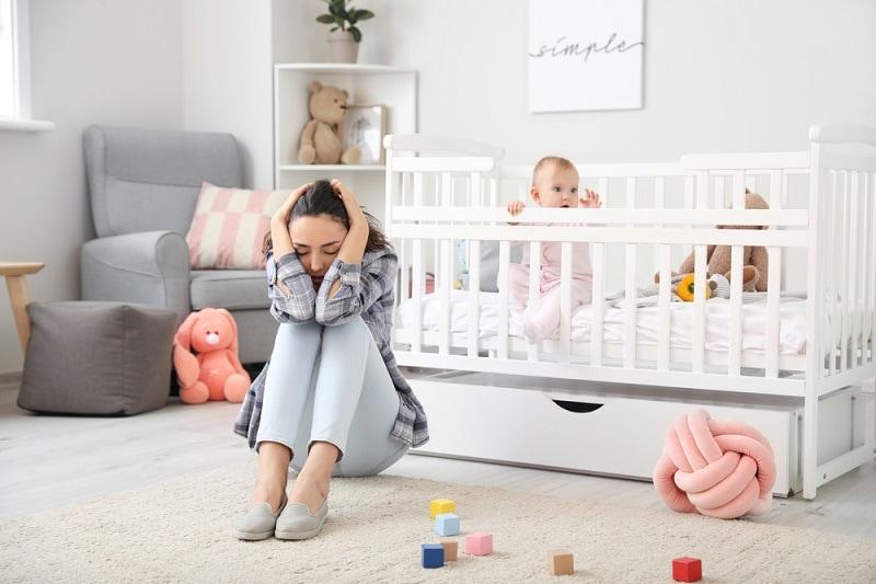 depressive junge Mutter sitzt auf dem Boden des Kinderzimmers