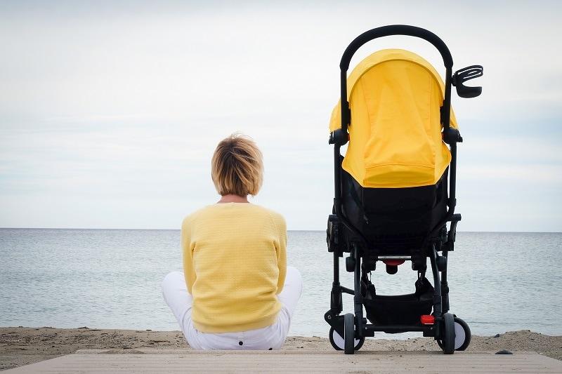 eine junge Mutter sitzt neben einem Kinderwagen und schaut auf den Horizont