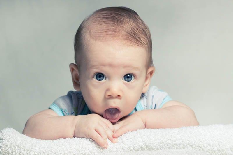 entzückender kleiner Junge mit modernem Haar, das Mund offen hält