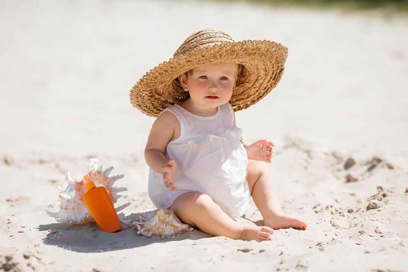 entzückendes kleines Mädchen mit Hut, der im Sand neben dem Sonnenschutz sitzt