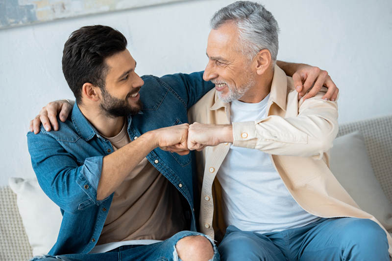 fröhliche Rentner Faust bumping mit glücklichen bärtigen Sohn zu Hause