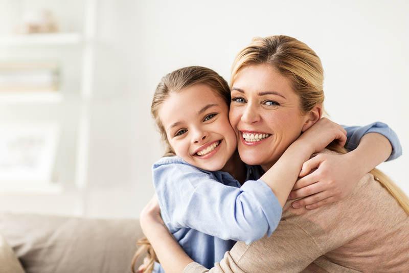 glücklich lächelndes Mädchen mit Mutter umarmt auf Sofa zu Hause