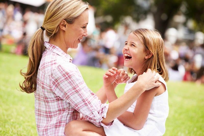 glückliche Mutter lachend mit Tochter im Freien auf dem Gras