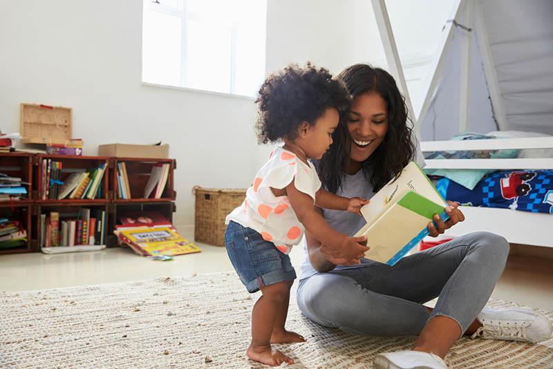 glückliche Mutter liest ein Buch mit ihrem Baby auf dem Zimmerboden