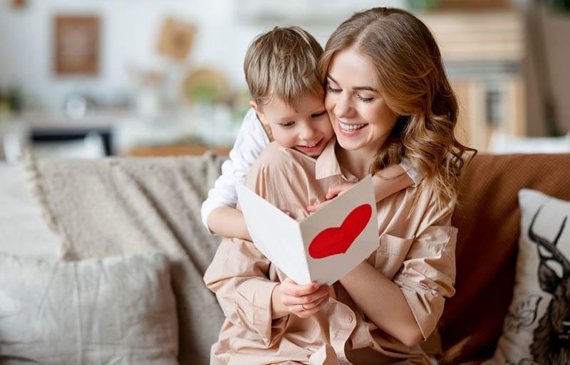 glückliche Mutter umarmt Sohn und Lesen Brief für Geburtstag