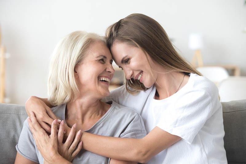 glückliche Mutter und Tochter umarmen sich auf der Couch