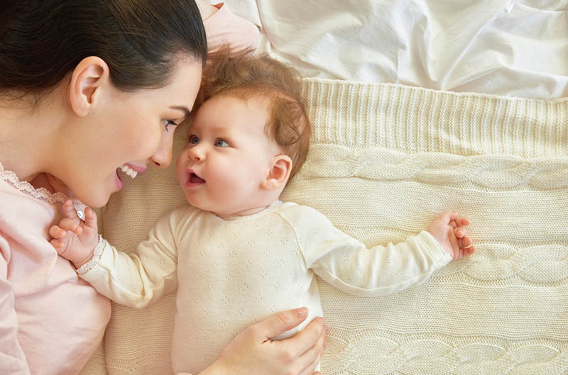 glückliche junge Mutter spielt mit ihrem Baby auf dem Bett