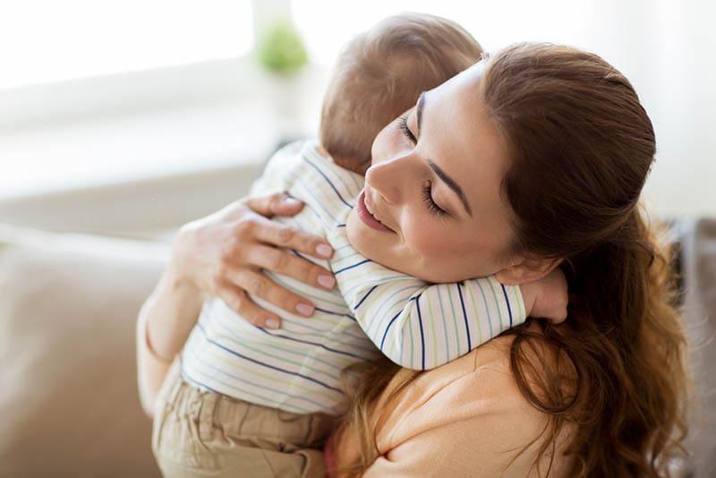glückliche junge Mutter umarmt fest mit ihrem kleinen Jungen zu Hause