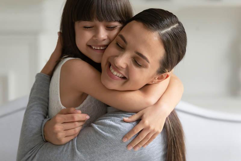 glückliche junge Mutter umarmt mit Tochter stark