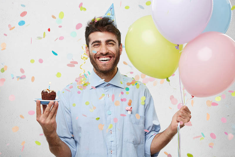 glücklicher Mann feiert Geburtstag mit Luftballons und einem Mini-Kuchen