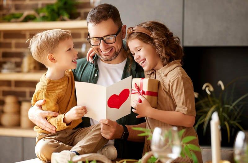 glücklicher Vater, der eine Karte von seinen Kindern zu Hause liest