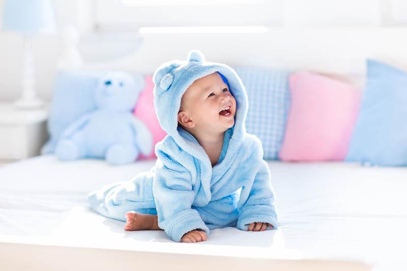glückliches Baby Junge trägt blaue Dusche stricken und sitzt auf dem Bett