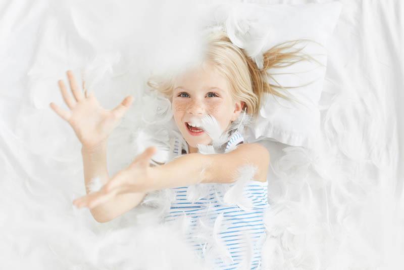 glückliches blondes kleines Mädchen, das auf dem Bett liegt und eine Feder in der Luft fängt