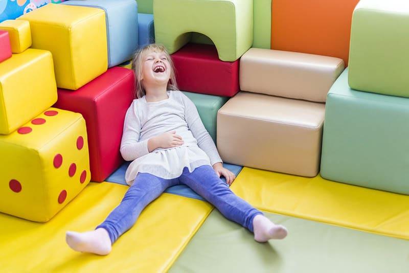 glückliches kleines Mädchen laut lachend auf dem bunten Spielplatz