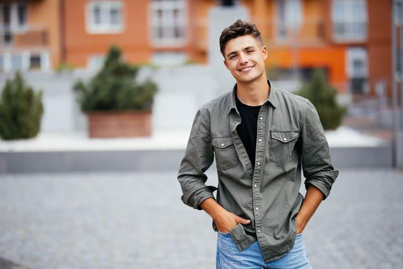 gut aussehender junger Mann lächelnd und posierend im Freien