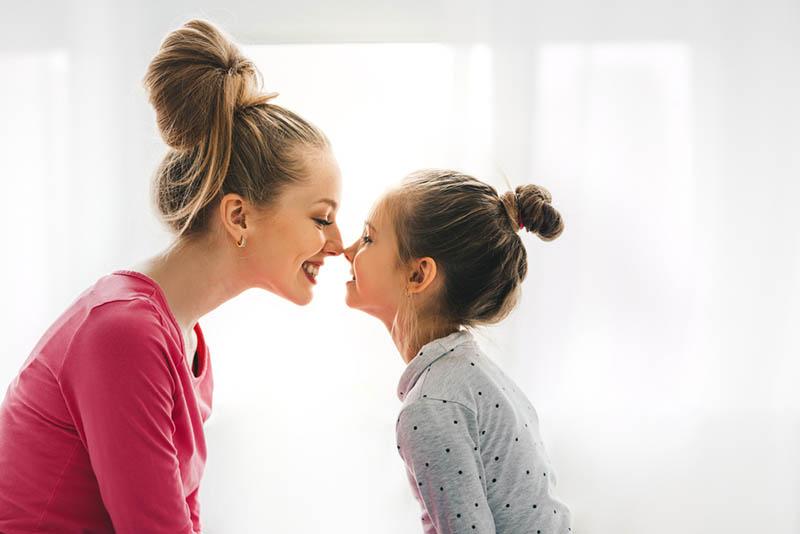 junge Mutter berührt mit Nasen mit ihrer Tochter