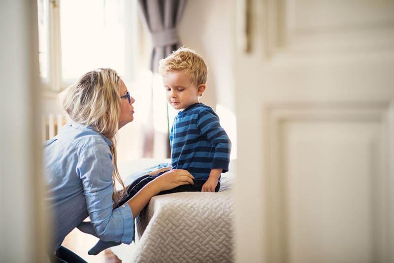 junge Mutter im Gespräch mit ihrem Kleinkind Sohn in einem Schlafzimmer