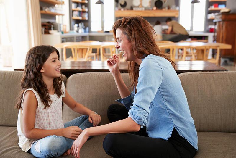 junge Mutter lachend mit Tochter auf der Couch zu Hause