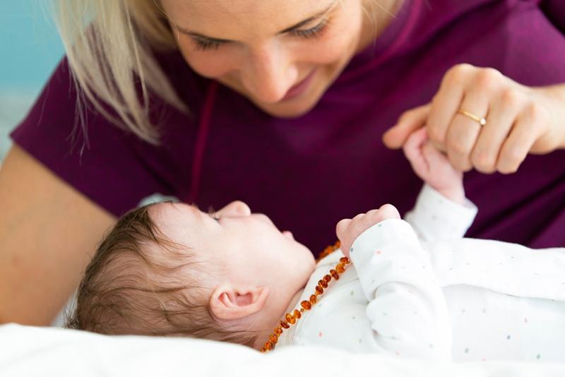 junge Mutter spielt mit ihrem Baby, das Bernsteinkette trägt