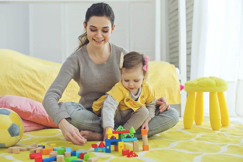 junge Mutter spielt mit ihrer süßen Tochter mit pädagogischen Spielzeug im Zimmer