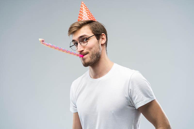junger Mann feiert Geburtstag und bläst Pfeife