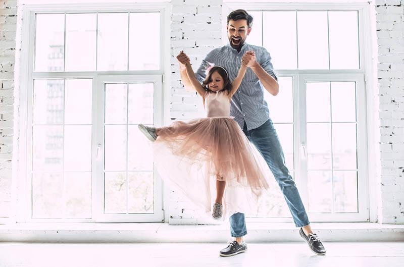 junger Vater tanzt mit seiner kleinen Tochter