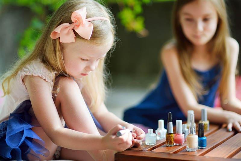 junges Mädchen macht ihren Nagellack und sitzt mit ihrer Freundin