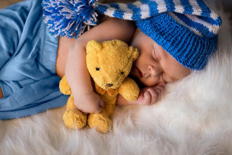 kleine neugeborene Junge umarmt Teddybär und schlafen