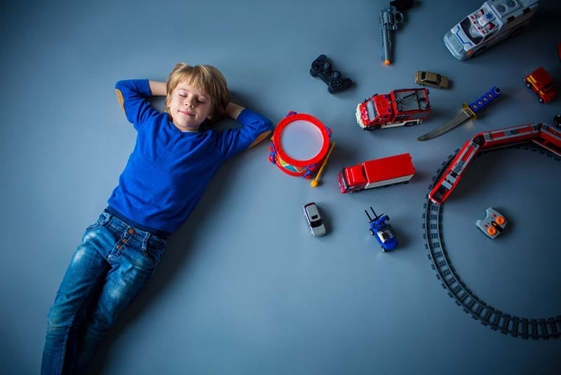 kleiner Junge auf dem Boden liegend mit Spielzeug