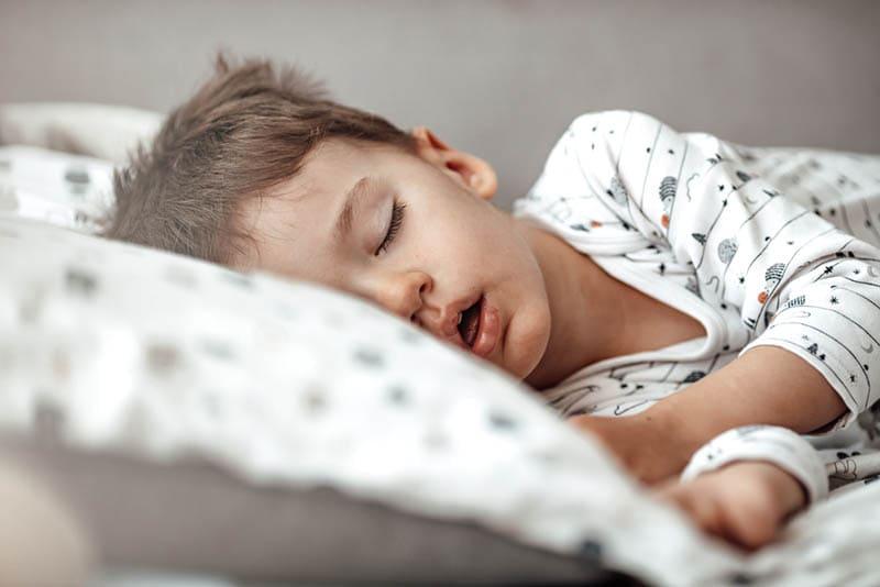 kleiner Junge schlafend im Bett in Pijama mit offenem Mund
