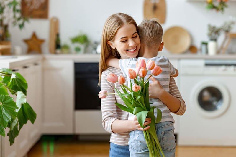 kleiner Junge umarmt seine Mutter mit Tulpen in ihren Händen