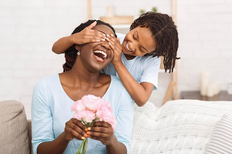 kleines Mädchen überrascht ihre Mutter mit Blumen