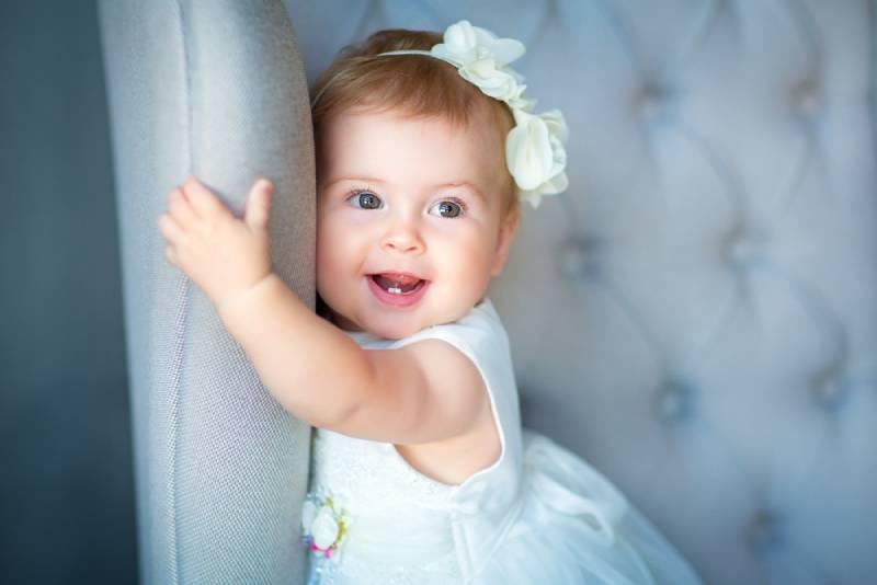lächelnd Baby Mädchen trägt weißes Kleid halten für Stuhl