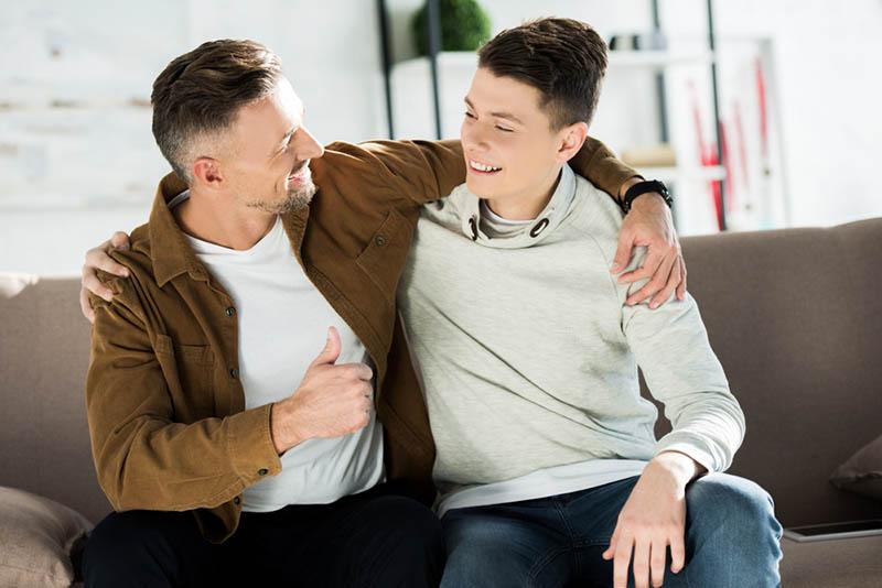 lächelnd Vater und Teenager-Sohn umarmt auf Sofa zu Hause