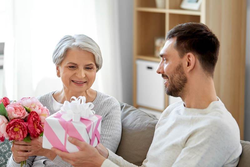 lächelnd erwachsenen Sohn geben Geschenk und Blumen zu seiner älteren Mutter zu Hause