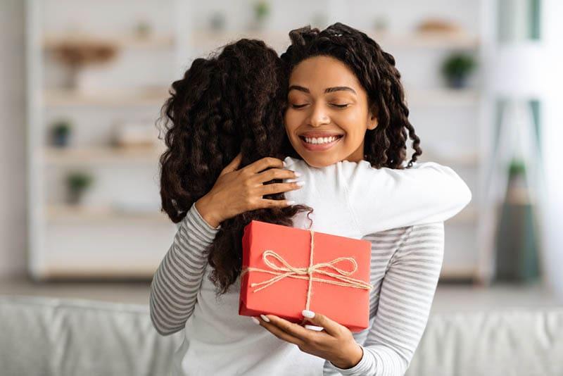 lächelnde Mutter, die ihre Tochter umarmt, während sie ein Geschenk hält