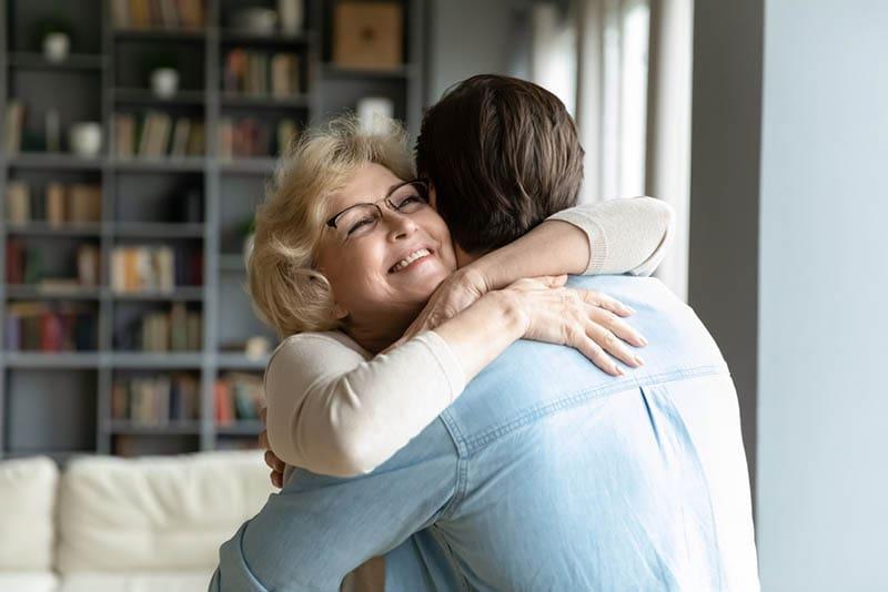 lächelnde Mutter, die ihren Sohn zu Hause umarmt