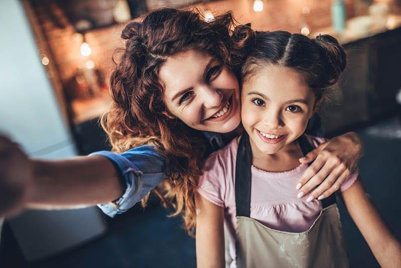 lächelnde Mutter nimmt Selfie mit ihrer süßen Tochter