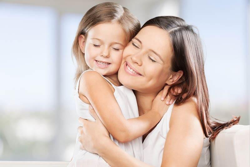 lächelnde Mutter und Tochter, die sich mit geschlossenen Augen umarmen