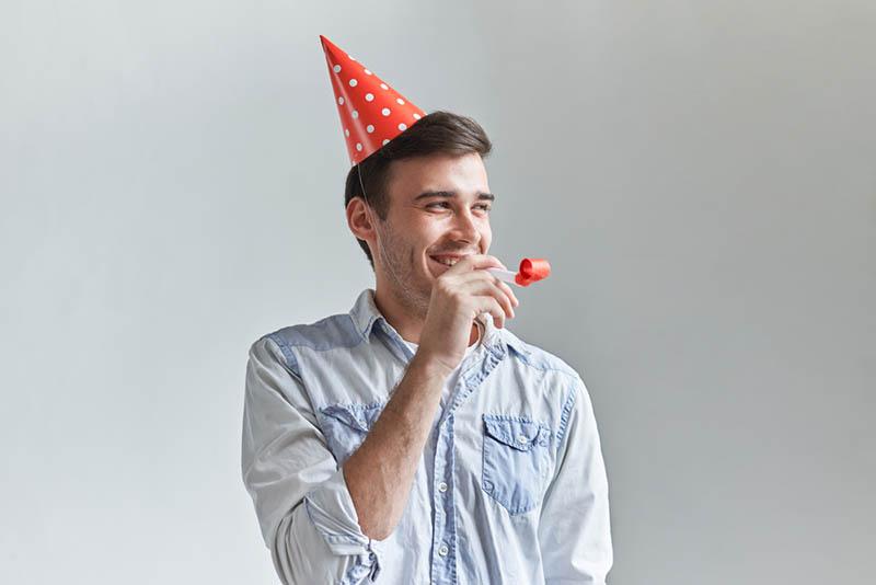 lächelnder Mann feiert Geburtstag mit Party-Pfeife