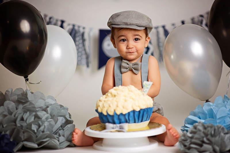 niedlichen kleinen Jungen sitzen mit seinem Geburtstagskuchen und Luftballons