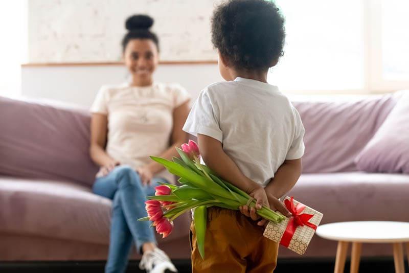 niedlichen kleinen Jungen versteckt Blumen und Geschenk vor seiner Mutter
