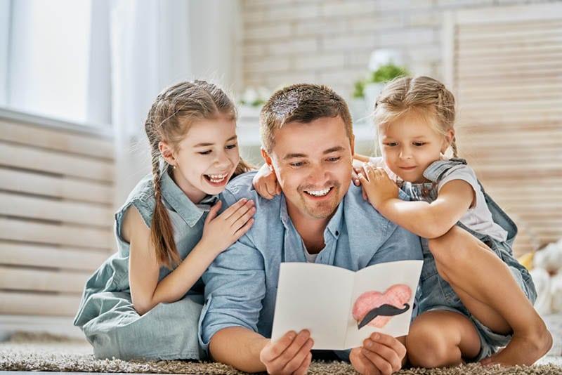 niedlichen kleinen Mädchen lesen Glückwunschkarte mit Papa