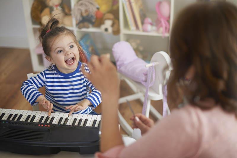 niedlichen kleinen Mädchen sitzen und singen mit ihrer Mutter neben dem Musikinstrument