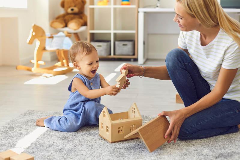 schöne Mutter gibt ein Spielzeug zu niedlichen Baby-Mädchen auf dem Boden