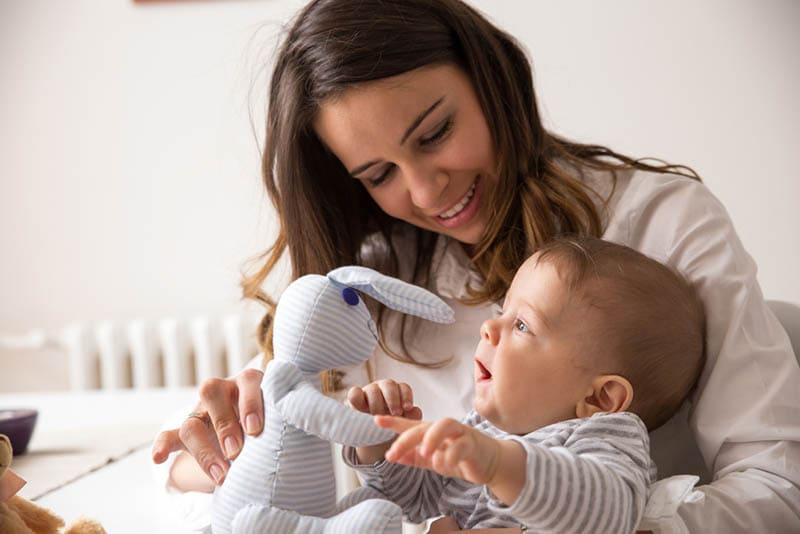 schöne Mutter spielt mit ihrem süßen Baby und einem Spielzeug