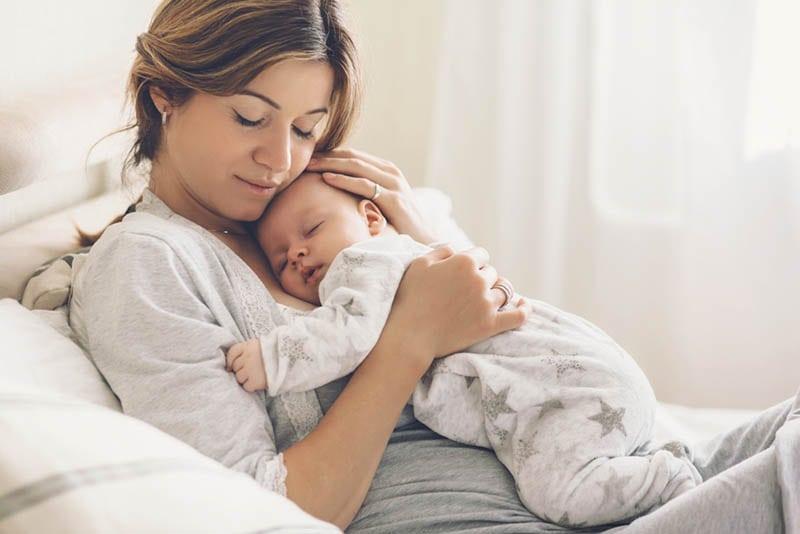 schöne junge Mutter hält schlafendes Baby auf Brust und kuscheln auf dem Bett
