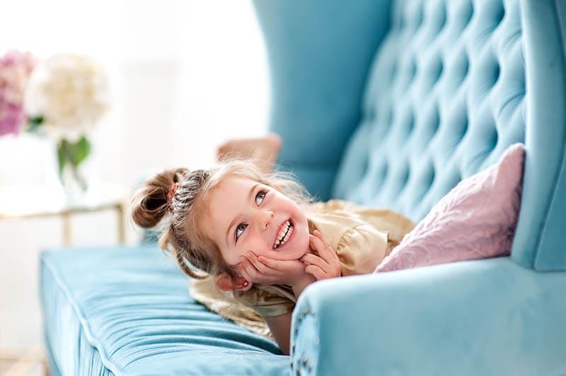 schöne kleine Mädchen spielen auf der blauen Couch zu Hause